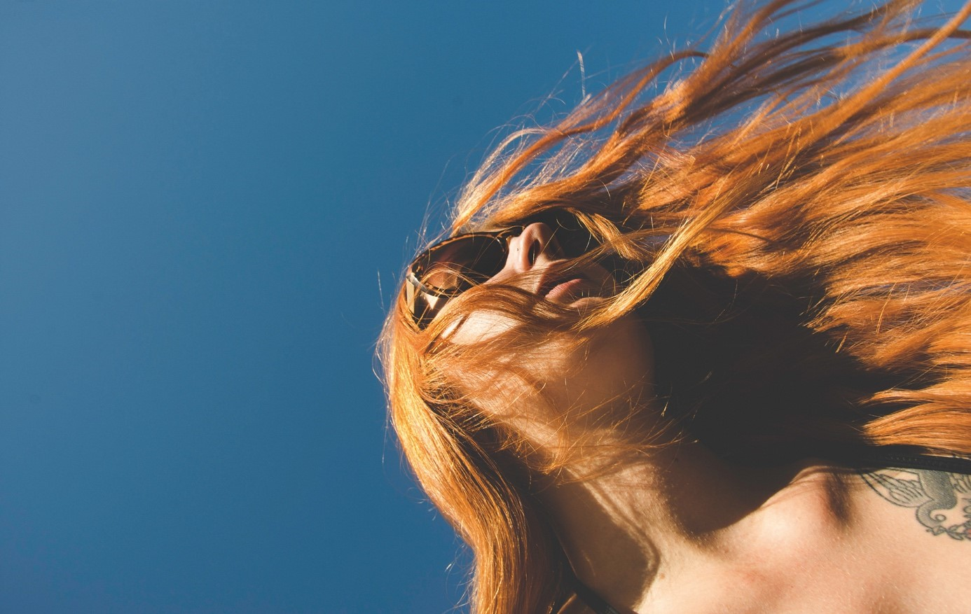 Red headed girl with a blue background, hair is swying in the wind, girl is wearing sunglasses